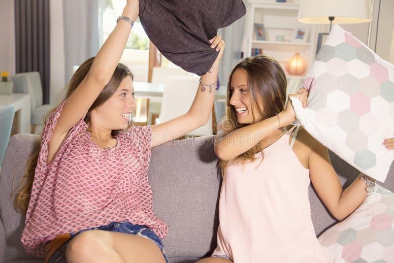 Gulliga flickor som hemma som gör kuddekampen skrattar skottet för lyckligt medel royaltyfri bild
