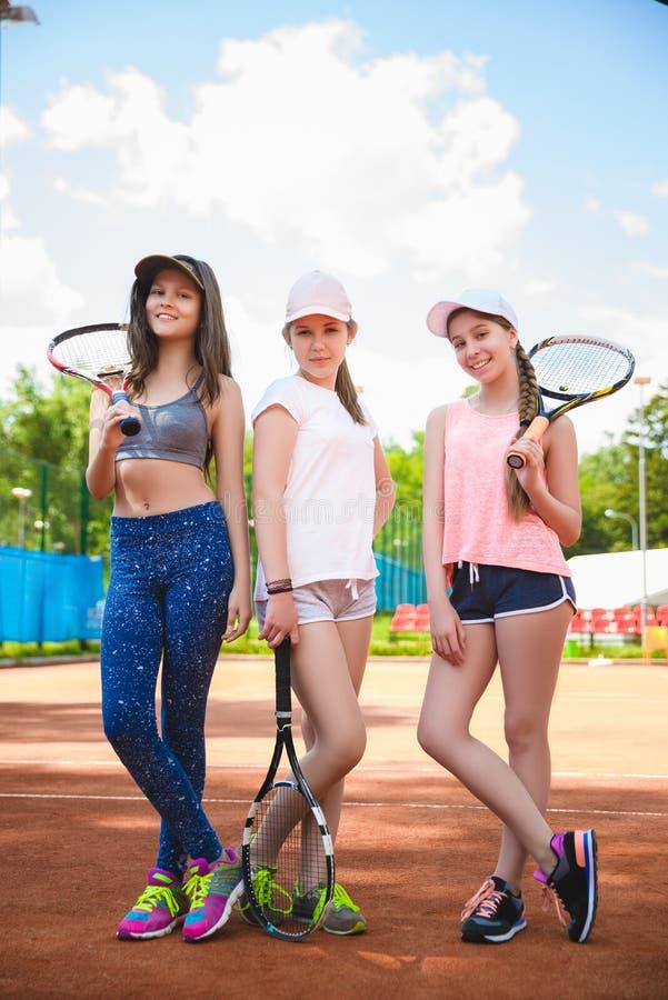 Gulliga flickor som spelar tennis och i rätten poserar utomhus- arkivbilder
