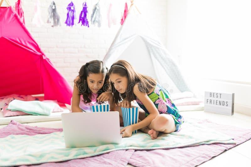 Gulliga flickor som tycker om film på bärbara datorn under Sleepoverpartiet arkivbild