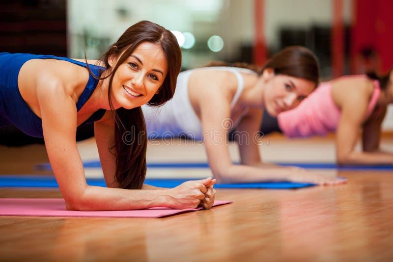Gulliga flickor som utarbetar i en idrottshall arkivfoton