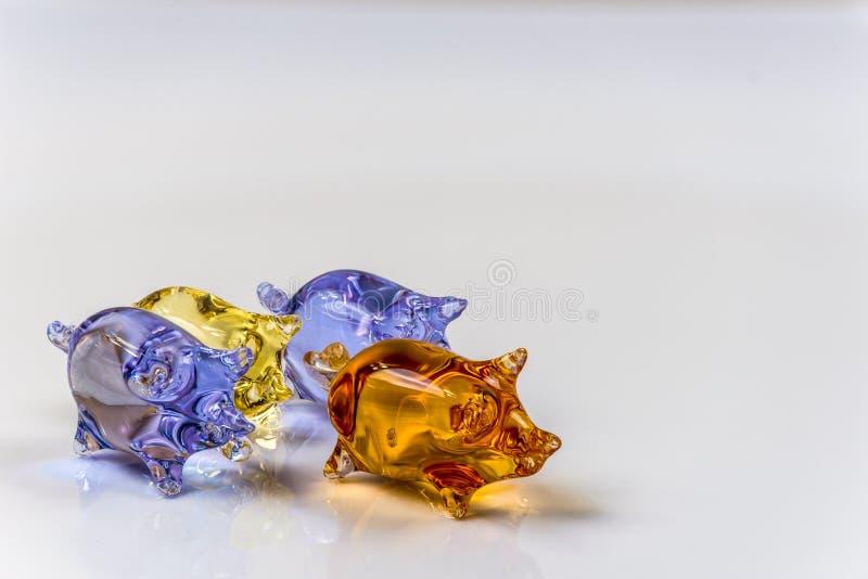 Gulliga glass svinstatyetter på ljus bakgrund arkivfoton