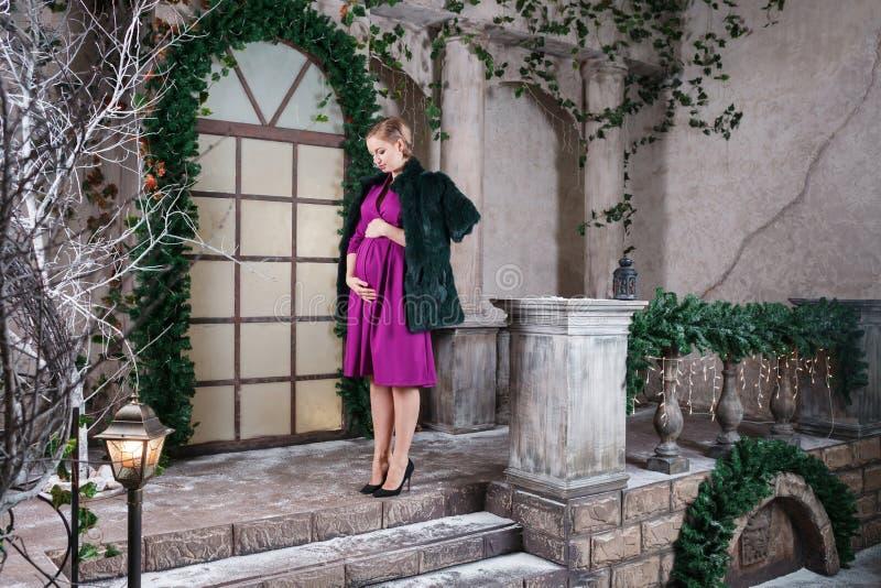 Gulliga gravida mammaställningar på härlig dekorerad jul terrasserar, lycklig havandeskaptid royaltyfri foto