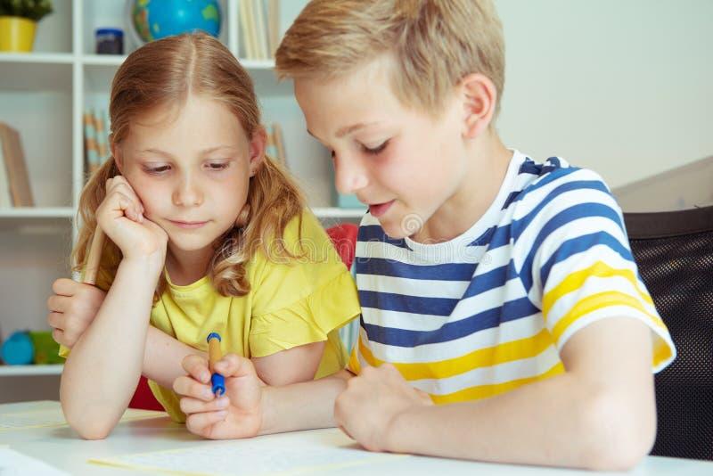 Gulliga klyftiga skolbarn är kom tillbaka till skola och att studera tillsammans på tabellen royaltyfria foton