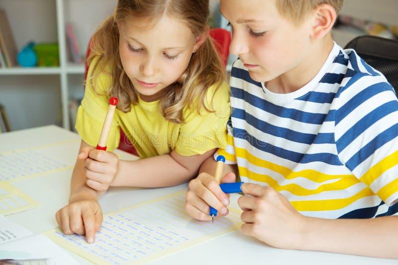 Gulliga klyftiga skolbarn är kom tillbaka till skola och att studera tillsammans på tabellen arkivbild