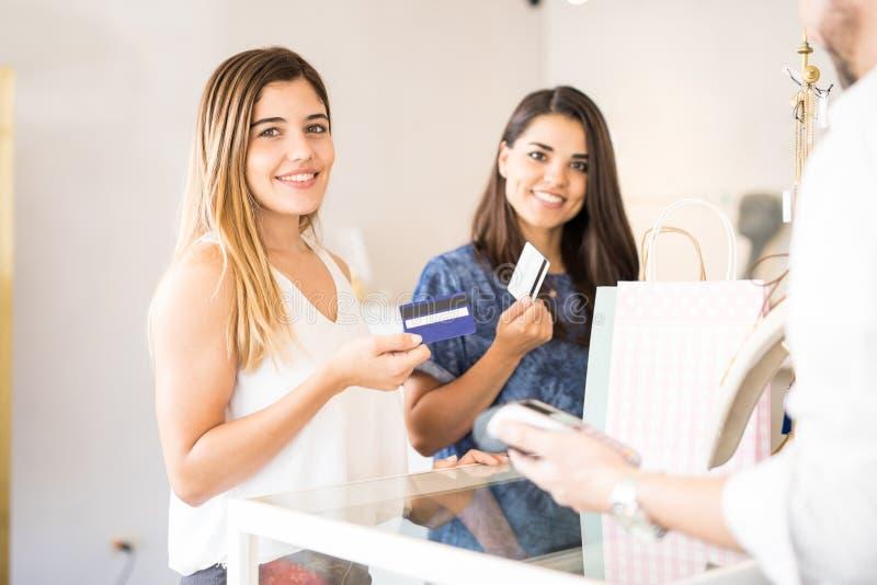 Gulliga kvinnliga vänner som tillsammans shoppar arkivfoto
