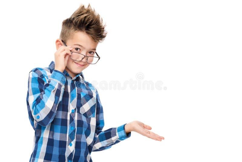 Gulliga le bärande läsningexponeringsglas för pojke och peka med handen till en sidostudiostående på vit royaltyfri fotografi