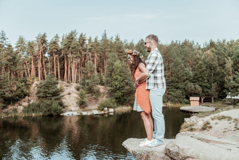 Gulliga lyckliga älska par som har, vilar nära den stora härliga sjön och vaggar tillsammans arkivbilder