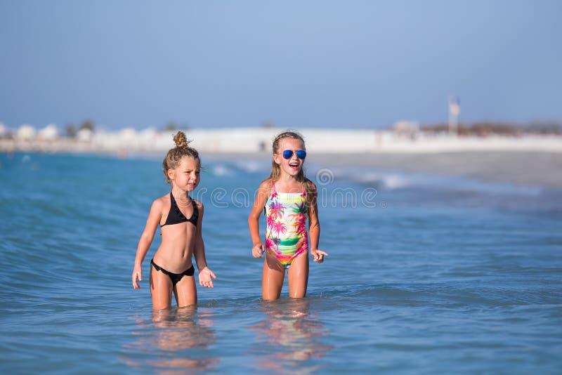 Gulliga lyckliga barn som spelar i havet på stranden arkivfoton