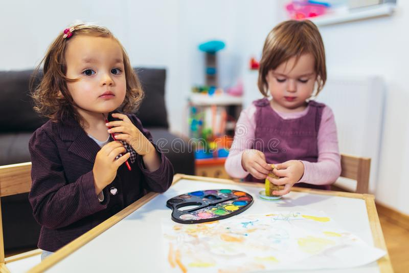 Gulliga lyckliga små flickor, förskolebarn, målning med vattenfärg arkivbilder