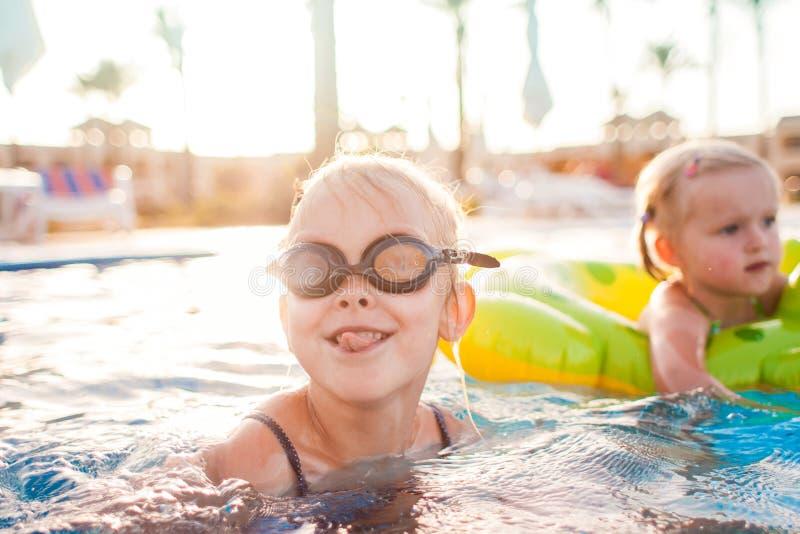 Gulliga lyckliga små flickor som har gyckel i simbassäng royaltyfri foto