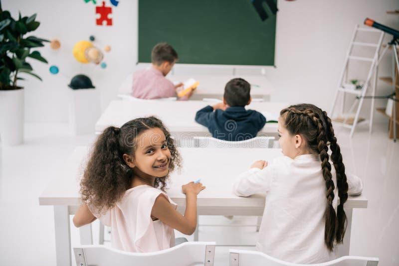 Gulliga multietniska ungar som sitter på skolaskrivbord och studing i klassrum arkivfoto