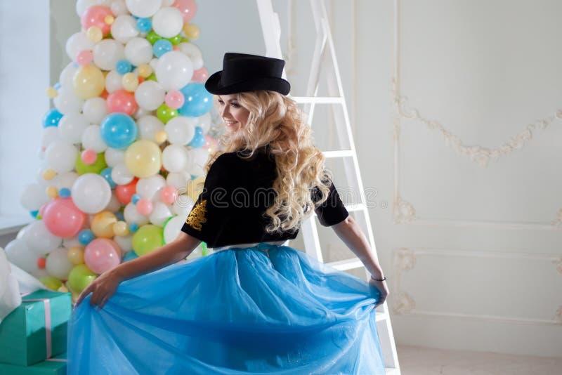 Gulliga och härliga blonda danser i en sagolik inre Den charmiga unga kvinnan i en curvy blått kringgår royaltyfri fotografi