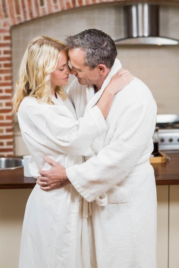 Gulliga par omkring som ska kyssas i badrockar royaltyfri foto