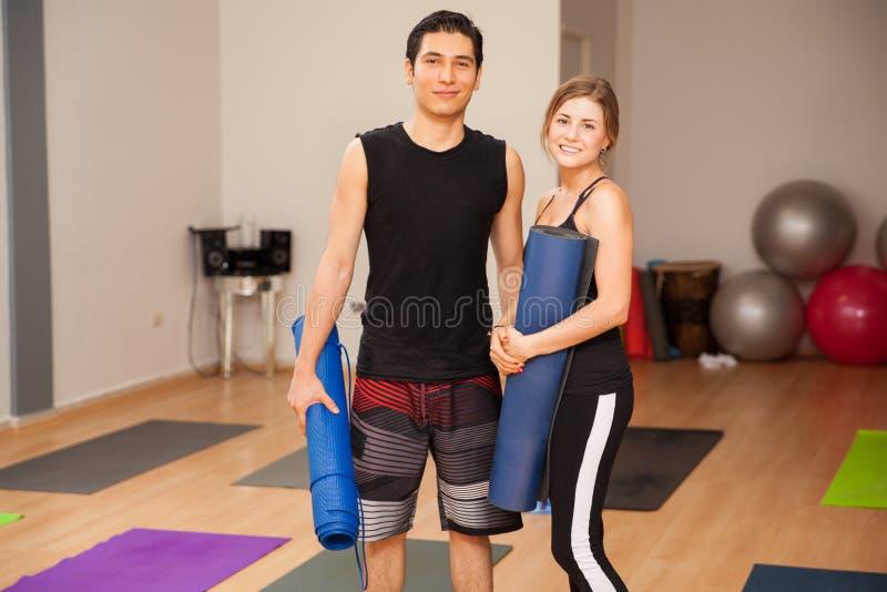 Gulliga par som är klara för yoga royaltyfri foto