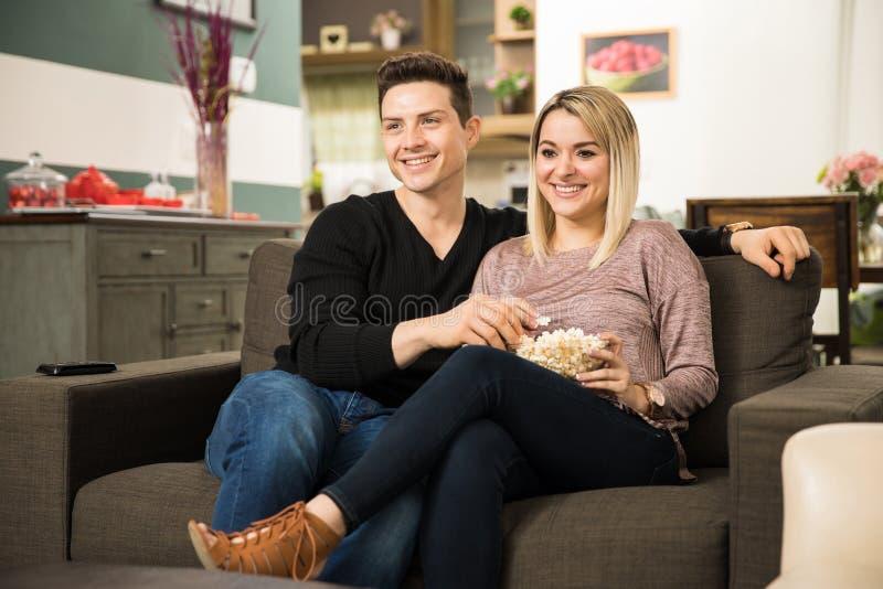 Gulliga par som håller ögonen på en komedi på TV arkivfoto