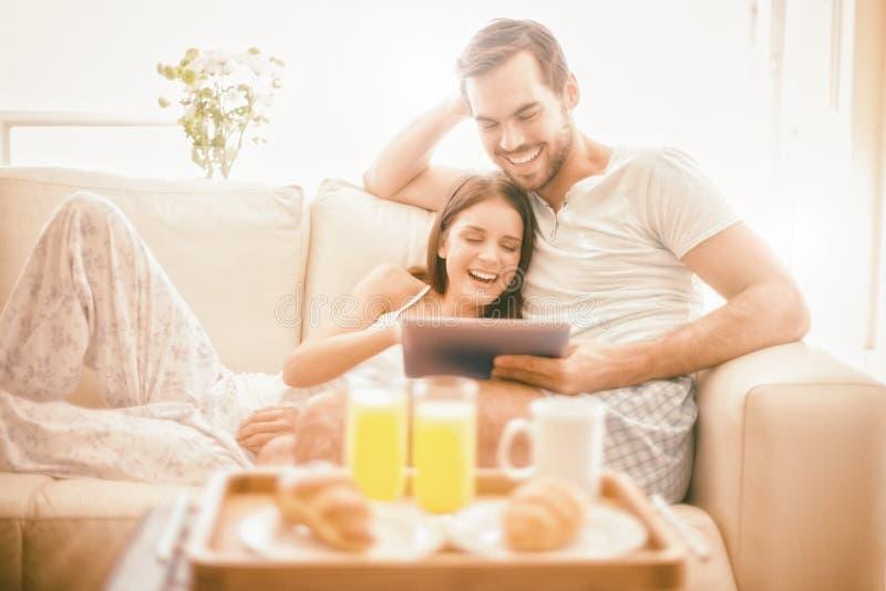 Gulliga par som kopplar av på soffan med minnestavlan på frukosten royaltyfri bild