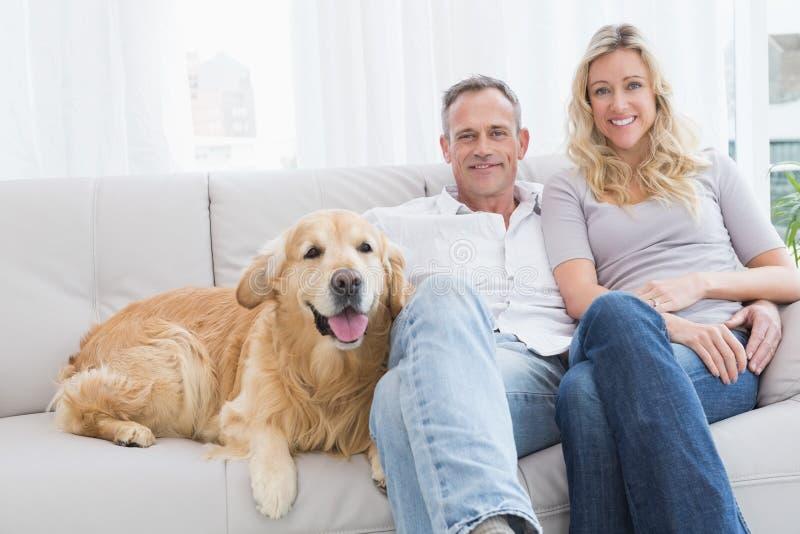 Gulliga par som tillsammans kopplar av på soffan med deras hund royaltyfria bilder