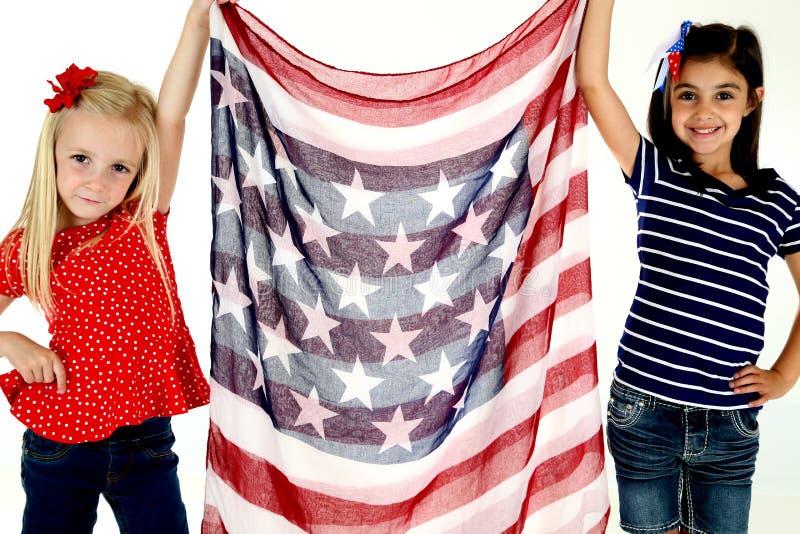 Gulliga patriotiska flickor som rymmer en amerikanska flagganhalsduk arkivbilder