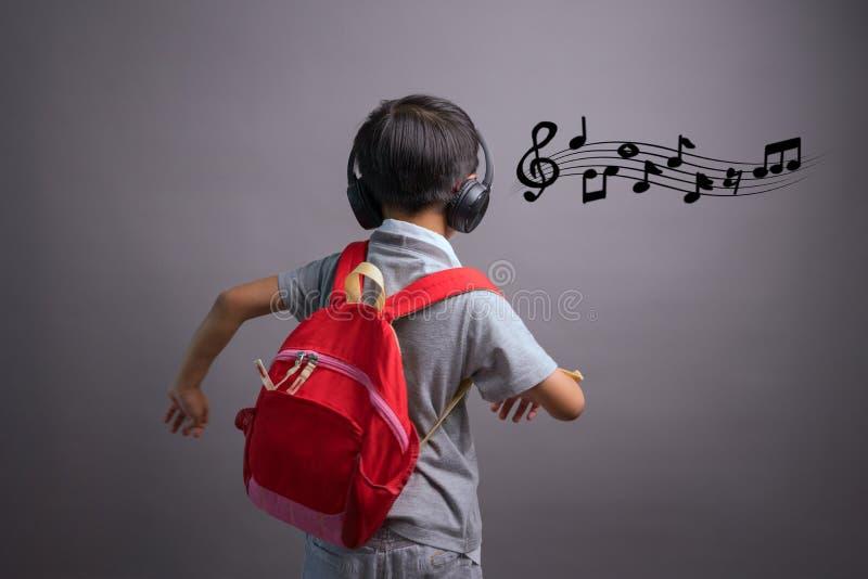 Gulliga roliga barn i dansstudion, gullig pys i h?rlurar som lyssnar till musik p? f?rgbakgrund royaltyfri fotografi