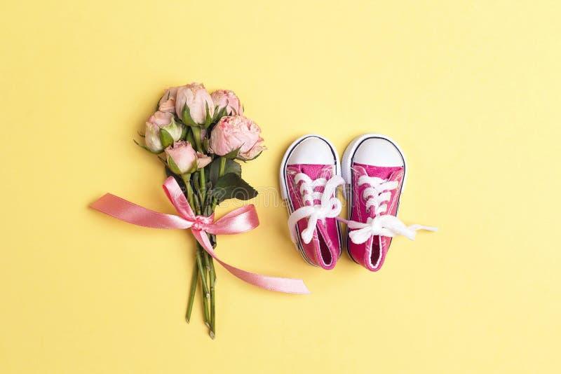 Gulliga rosa färger behandla som ett barn flickagymnastikskor med den lilla buketten av rosor på en gul bakgrund royaltyfri foto