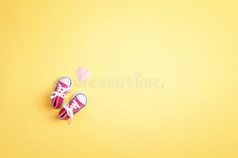 Gulliga rosa färger behandla som ett barn flickagymnastikskor med hjärta på en gul bakgrund kopiera avst?nd royaltyfria bilder