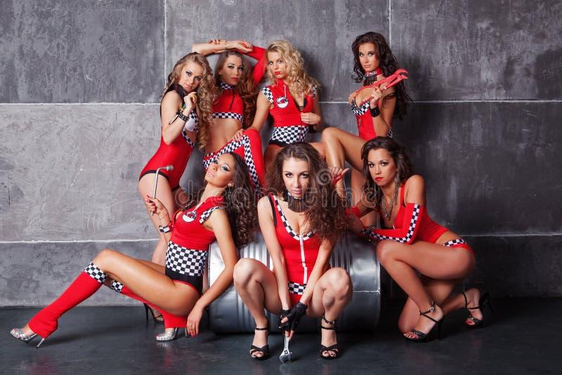 Gulliga sju gå-går sexiga flickor i röd tävlings- dräkt royaltyfri bild