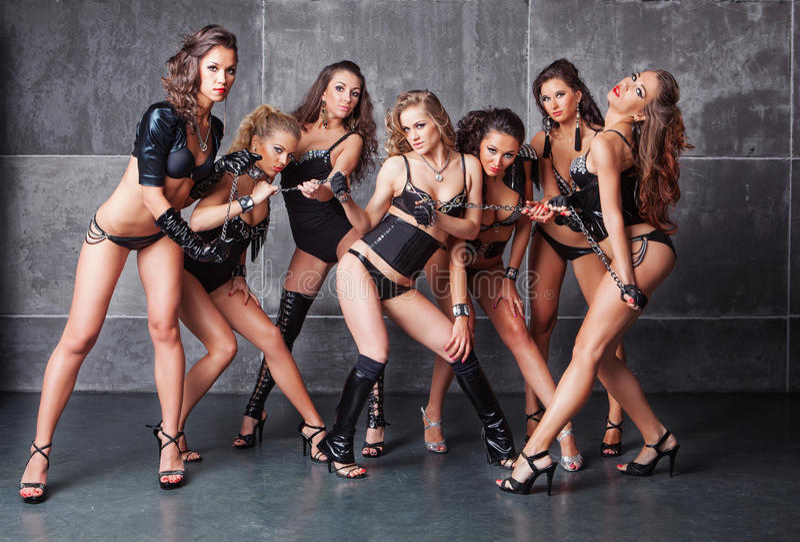 Gulliga sju gå-går sexiga flickor i svart med diamanter arkivbilder