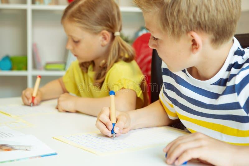 Gulliga skolbarn ?r kom tillbaka till skolan och att l?ra p? tabellen i klassrum fotografering för bildbyråer