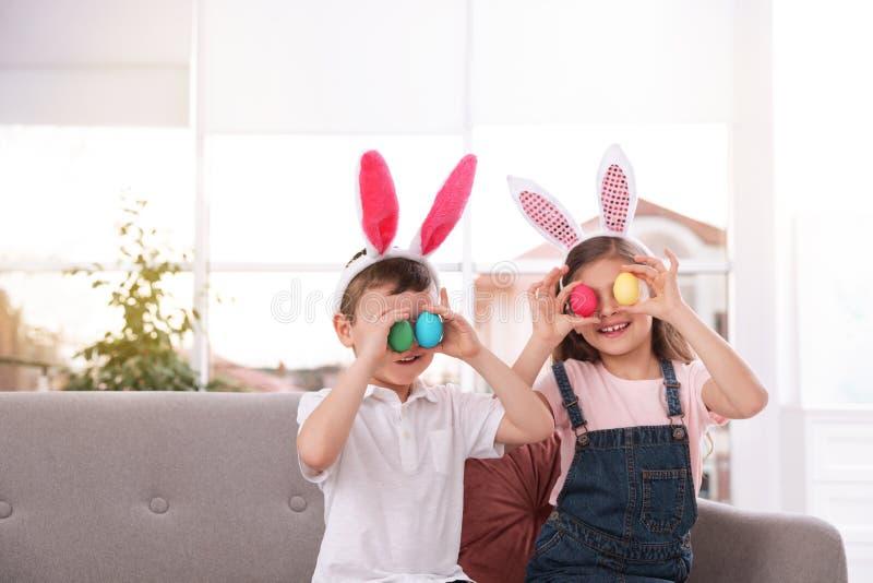 Gulliga små barn i kaninörahuvudbindlar som hemma rymmer påskägg nära ögon royaltyfri fotografi