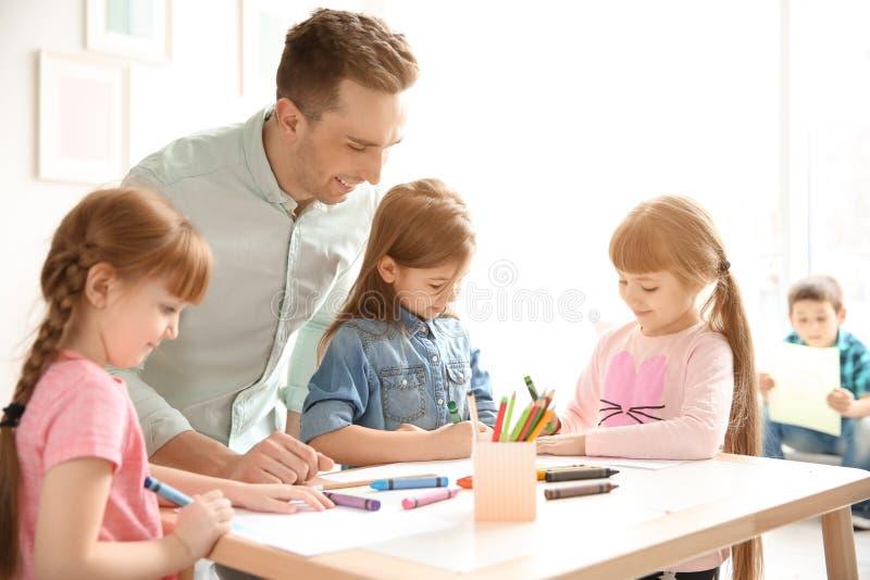 Gulliga små barn med läraren i klassrum royaltyfri bild