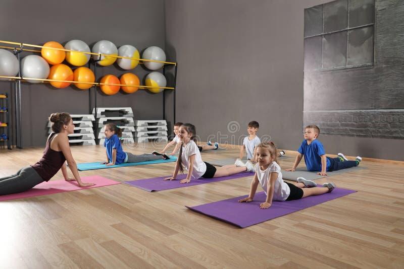 Gulliga små barn och instruktör som gör fysisk övning i skolaidrottshall arkivbilder