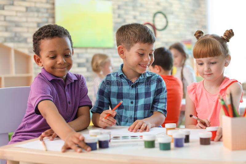 Gulliga små barn som inomhus målar på tabellen royaltyfri bild