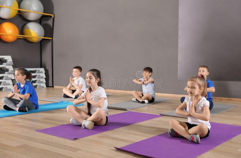 Gulliga små barn som sitter på golv och gör fysisk övning i skolaidrottshall arkivfoton