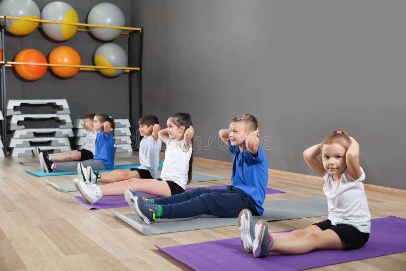 Gulliga små barn som sitter på golv och gör fysisk övning i skolaidrottshall royaltyfri fotografi