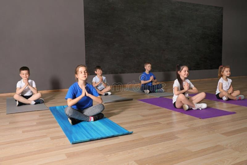 Gulliga små barn som sitter på golv och gör fysisk övning i skolaidrottshall royaltyfria foton