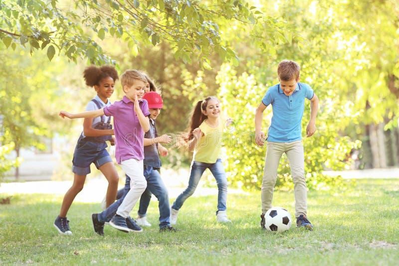 Gulliga små barn som spelar med bollen utomhus arkivfoto