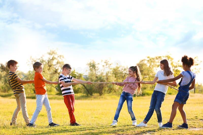 Gulliga små barn som spelar med repet utomhus royaltyfri fotografi