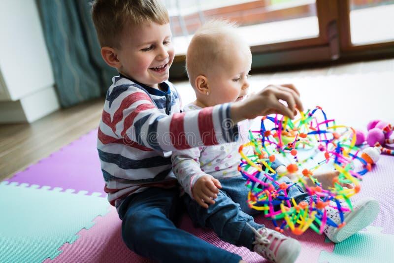 Gulliga små barn som spelar, medan sitta på matta arkivbild