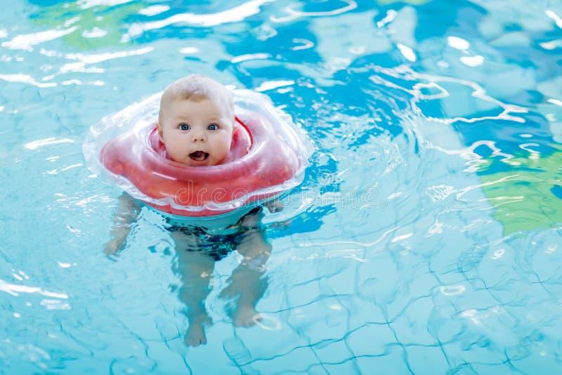 Gulliga små behandla som ett barn barnet som lär att simma med simningcirkeln i en inomhus pöl nyfödd flicka eller pojke som har  royaltyfria foton
