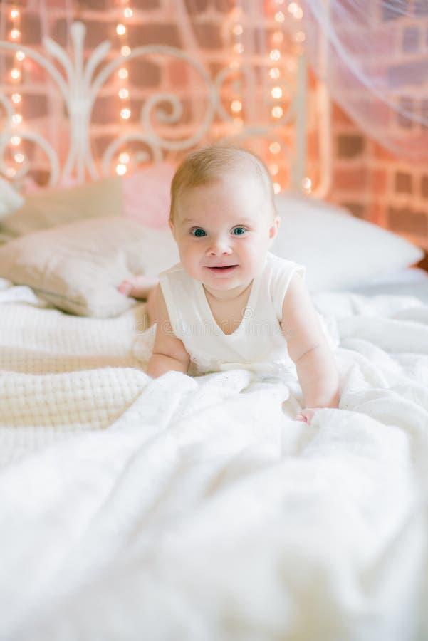 Gulliga små behandla som ett barn flickan i vit kläder som hemma ligger på sängen fotografering för bildbyråer