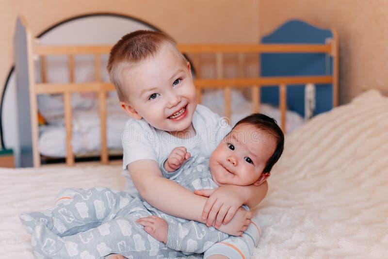 Gulliga små behandla som ett barn med äldre broder som hemma ligger på säng arkivfoto