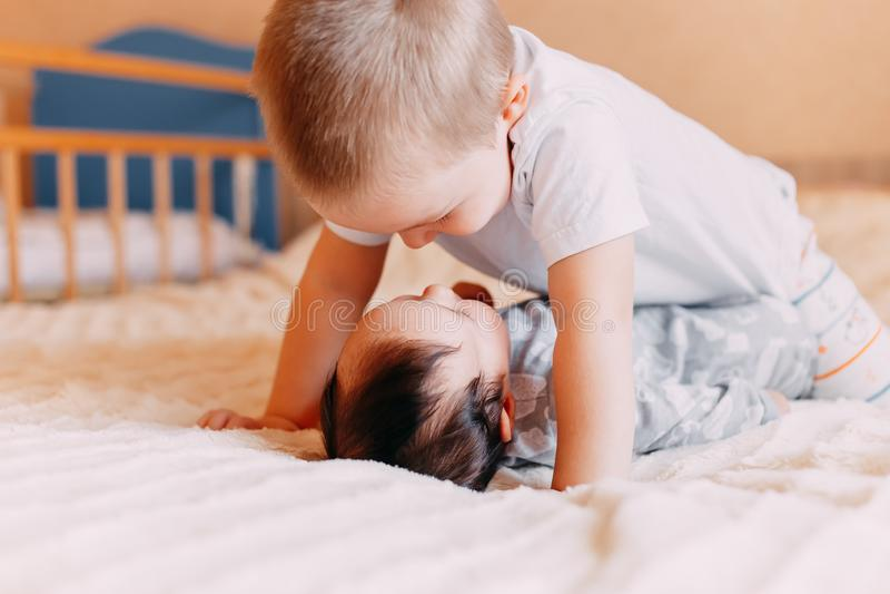 Gulliga små behandla som ett barn med äldre broder som hemma ligger på säng royaltyfri fotografi