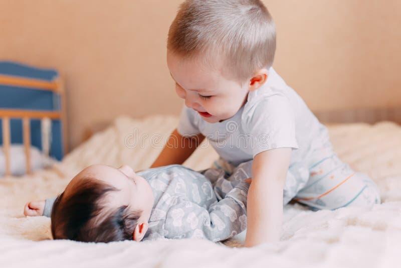 Gulliga små behandla som ett barn med äldre broder som hemma ligger på säng arkivbilder