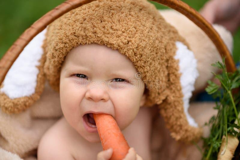 Gulliga små behandla som ett barn pojken i dräkt av kaninsammanträde på gräset i korg som äter kål och moroten arkivbilder