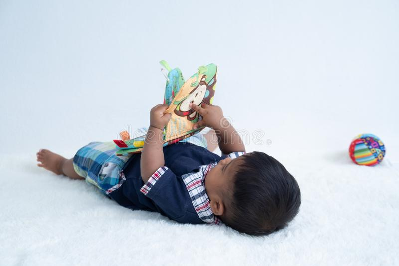 Gulliga små behandla som ett barn pojken som läser boken royaltyfri fotografi