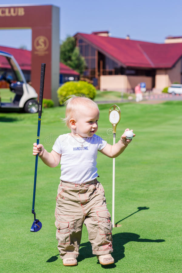 Gulliga små behandla som ett barn pojken som spelar golf på ett fält royaltyfri foto