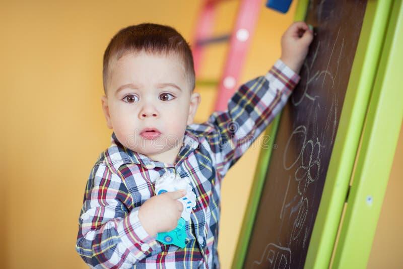 Gulliga små behandla som ett barn pojketeckningen med färgrik krita arkivbilder
