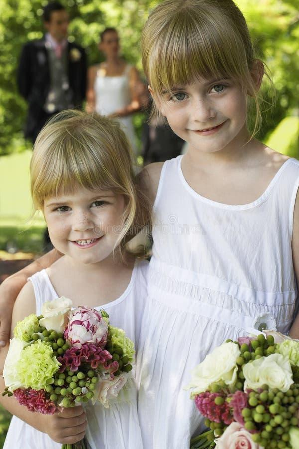 Gulliga små brudtärnor som rymmer buketter royaltyfri fotografi