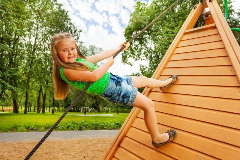 Gulliga små flickaklättringar på träkonstruktion royaltyfria bilder