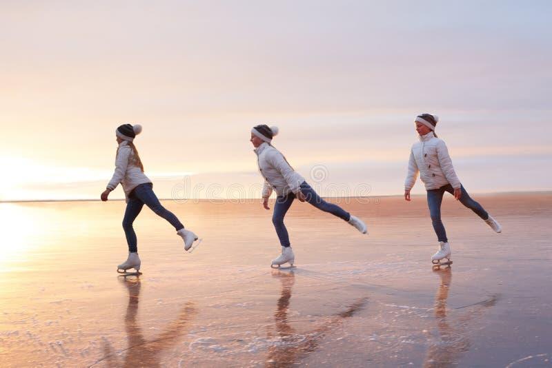 Gulliga små flickor åker skridskor på en djupfryst sjö silhouette royaltyfria foton